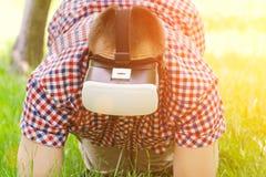 戴虚拟现实眼镜的人在他的在绿草的膝盖站立 免版税库存图片