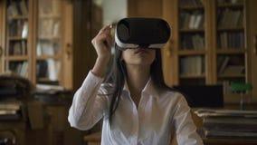 戴虚拟现实眼镜的年轻浅黑肤色的男人在面孔的有时间在图书馆