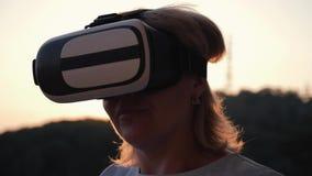 戴虚拟现实眼镜的白肤金发的女孩在日落 现代技术 真正生活和通信 股票视频