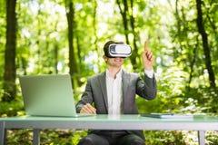 戴虚拟现实眼镜的确信的英俊的商人指向了与手指办公桌在绿色公园 到达天空的企业概念金黄回归键所有权 免版税图库摄影