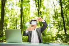 戴虚拟现实眼镜的确信的英俊的商人指向了用手办公桌在绿色公园 到达天空的企业概念金黄回归键所有权 库存图片