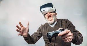 戴虚拟现实风镜/VR眼镜的成熟人使用 免版税库存图片