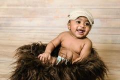 戴被编织的帽子的婴儿混合的族种健康看的男婴坐在嘘一个蓬松毛茸的篮子木背景现代演播室 免版税库存照片