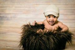戴被编织的帽子的婴儿混合的族种健康看的男婴坐在嘘一个蓬松毛茸的篮子木背景现代演播室 免版税图库摄影