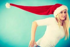 戴被风吹圣诞老人帽子的妇女 免版税图库摄影