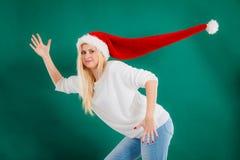 戴被风吹圣诞老人帽子的妇女 免版税库存图片