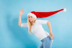 戴被风吹圣诞老人帽子的妇女 库存照片
