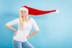 戴被风吹圣诞老人帽子的妇女 免版税库存照片