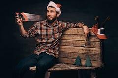 戴装饰的圣诞老人帽子的木匠坐一个木调色板 免版税库存图片