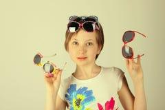 戴质朴的太阳镜的一个小女孩的特写镜头画象 免版税图库摄影