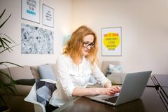 戴长的红色头发和眼镜的少妇看法工作的,在坐在明亮的一张木桌上的一个灰色膝上型计算机键盘的印刷品 库存图片