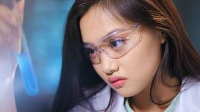 戴防护眼镜的特写镜头亚洲女性医疗保健专业工作者混合化学制品 股票录像