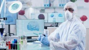 戴防护衣裳、面具和眼镜的男性化学家画象 影视素材
