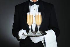 戴香宾眼镜的斟酒服务员在盘 免版税图库摄影