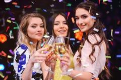 戴香槟眼镜的三个相当女孩  免版税图库摄影