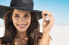戴黑帽会议的妇女在海滩 图库摄影