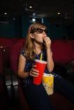 戴3D眼镜的女孩,当吃玉米花在电影期间时 免版税库存照片