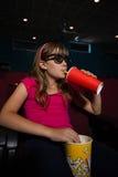 戴3D眼镜的女孩,当饮用饮料和玉米花在电影期间时 图库摄影