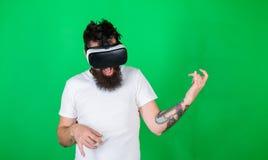 戴VR眼镜的人学会演奏在吉他的音乐 热心面孔用途现代技术的行家吉他弹奏者为 免版税库存图片