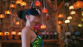 戴VR眼镜的旅游妇女购物在与传统土耳其灯的纪念品店的 股票录像