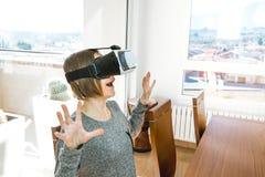 戴VR眼镜的激动和愉快的年轻女人 当前技术的概念与虚拟现实玻璃的 免版税库存照片