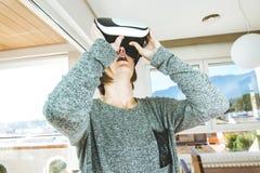 戴VR眼镜的激动和愉快的年轻女人 当前技术的概念与虚拟现实玻璃的 免版税库存图片
