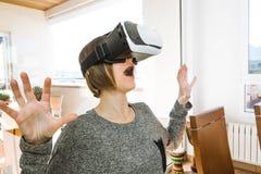 戴VR眼镜的激动和愉快的年轻女人 当前技术的概念与虚拟现实玻璃的 库存照片
