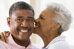 户内亲吻放松的微笑的夫妇 免版税库存图片