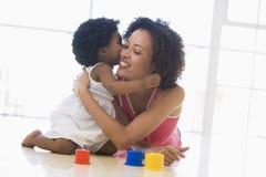 户内亲吻母亲的女儿 免版税库存照片