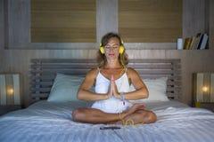 户内听到与耳机的音乐的美好和适合的健康女子30s实践的瑜伽画象在摆在安静的床上和 图库摄影