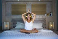 户内听到与耳机的音乐的美好和适合的健康女子30s实践的瑜伽画象在摆在安静的床上和 免版税图库摄影