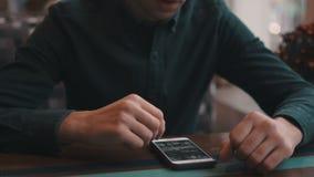 户内和观看的照片坐一个移动设备人的特写镜头 咖啡馆,舒适大气 股票视频