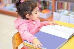 户内女孩在书前面 逗人喜爱的年轻小孩坐椅子在表和看书附近 库存图片