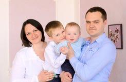 户内妈妈、爸爸和两个小儿子 免版税库存照片