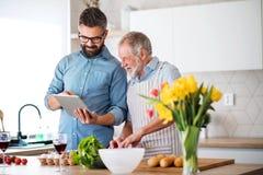 户内成人行家儿子和资深父亲在家厨房里,使用片剂 库存照片