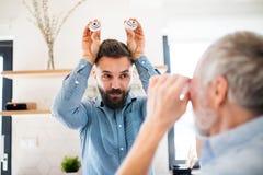 户内成人行家儿子和资深父亲在家厨房里,获得乐趣 免版税图库摄影
