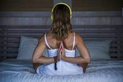 户内放松美好和适合的健康女子30s实践的瑜伽后面画象在床安静和集中在凝思n 免版税库存照片
