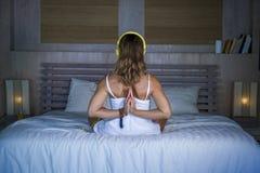 户内放松美好和适合的健康女子30s实践的瑜伽后面画象在床安静和集中在凝思n 库存图片