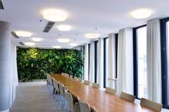 户内生存绿色墙壁、垂直的在人为照明设备下的庭院与花和植物在会议会议室里 库存图片