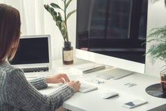 户内研究膝上型计算机和计算机的少妇自由职业者家庭办公室概念便装样式 免版税库存图片
