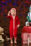 户内红色圣诞节服装的小孩 库存图片