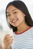 户内饮用的女孩挤奶微笑的年轻人 免版税图库摄影