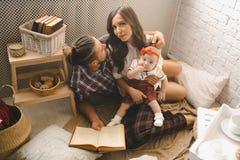 户内年轻家庭读书故事 免版税库存图片