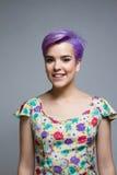 户内紫罗兰色短发妇女,微笑对照相机 免版税库存图片