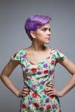 户内紫罗兰色短发妇女,站立用她的手在他 图库摄影
