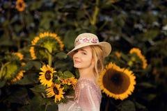 户外一个农村领域场面的美丽的妇女,用向日葵 免版税库存照片