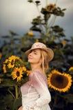 户外一个农村领域场面的美丽的妇女,用向日葵 库存照片