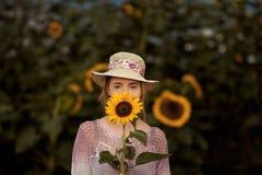 户外一个农村领域场面的美丽的妇女,用向日葵 免版税库存图片