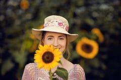 户外一个农村领域场面的美丽的妇女,用向日葵 库存图片