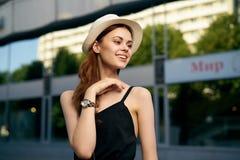户外一个白色帽子和一件黑礼服的年轻美丽的妇女在夏天在夏天 库存图片